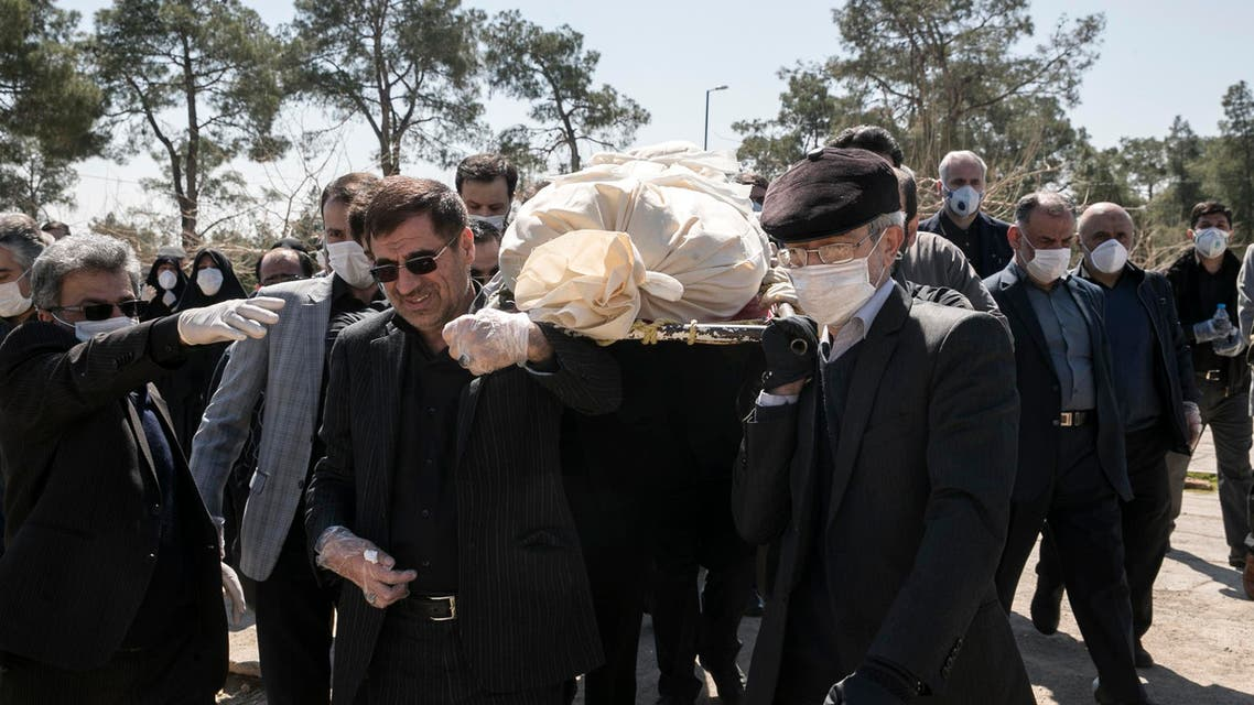 Mourners wearing face masks and gloves carry the body of former politburo official in the Revolutionary Guard Farzad Tazari, who died Monday after being infected with the new coronavirus, at the Behesht-e-Zahra cemetery just outside Tehran, Iran, on Tuesday, March 10, 2020. (AP)