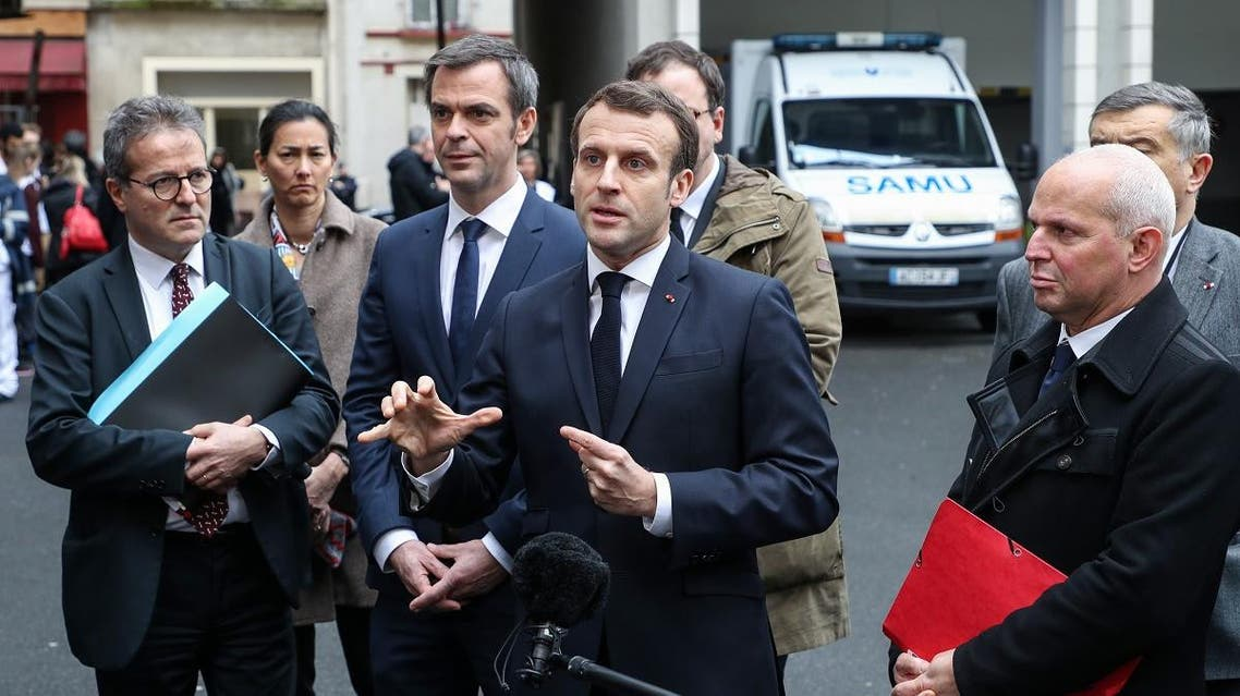 French President Emmanuel Macron speaks to the press as he leaves with (from L) AP-HP President Martin Hirsch, French Health and Solidarity Minister Olivier Veran, and French director general of health Jerome Salomon, after a visit of the SAMU-SMUR emergency services call center at the Necker Hospital on March 10, 2020 in Paris, focused on COVID-19 coronavirus outbreak. (AFP)