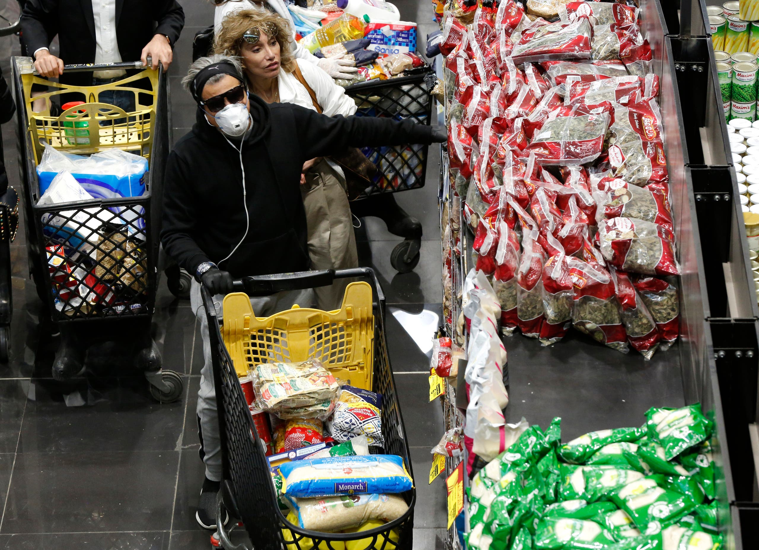 People shop at a supermarket as Lebanese begin to stock up on provisions, in Beirut on March 11, 2020. (AP)