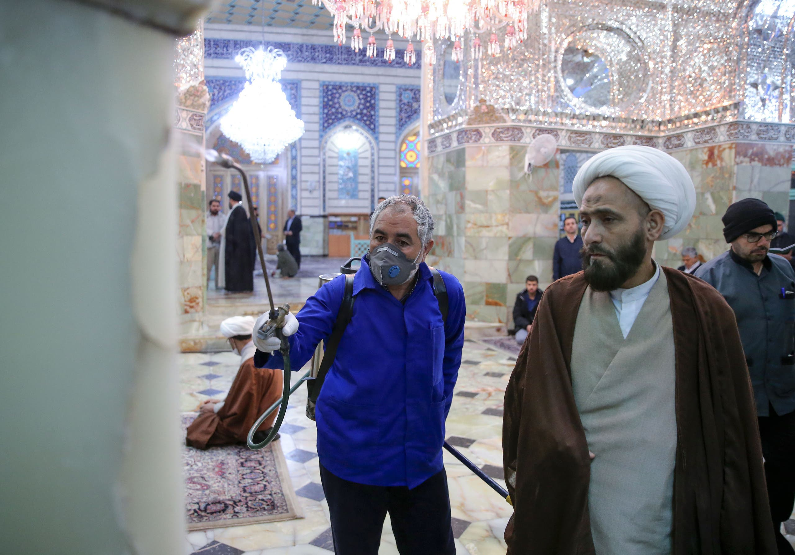A cleric looks at an Iranian sanitary worker disinfecting Qom's Masumeh shrine on February 25, 2020. (AP)