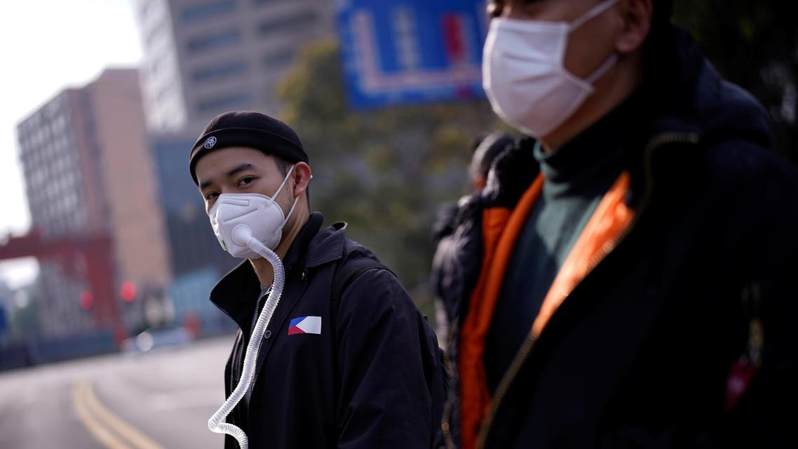 People wearing protective face masks are seen on a crossroads as the country is hit by an outbreak of the coronavirus, in Shanghai, China, March 10, 2020. (Reuters)