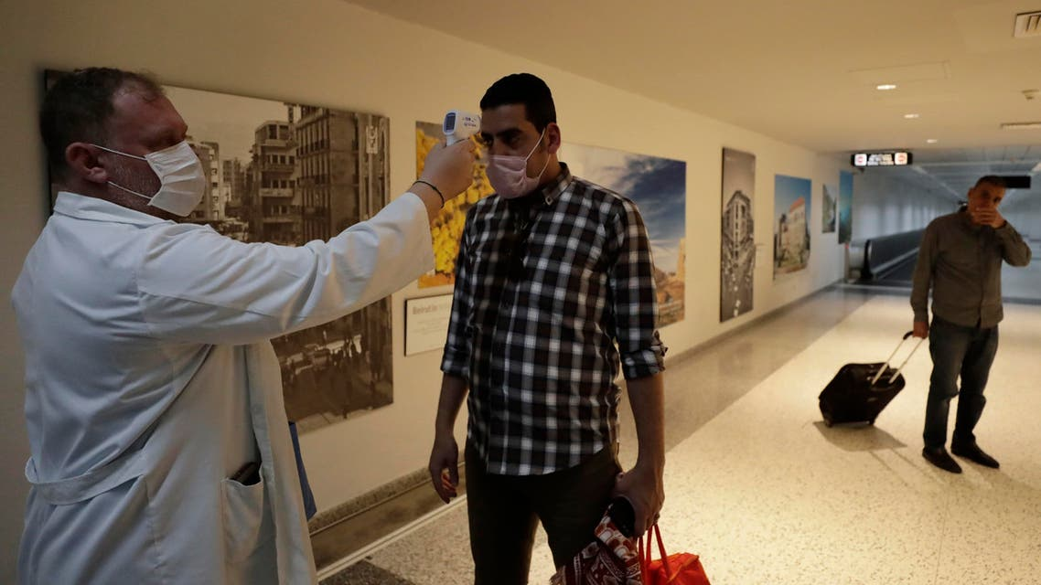 A passenger has his temperature checked as a precaution against a new coronavirus upon his arrival at the Rafik Hariri International Airport in Beirut on March 9, 2020. (AP)