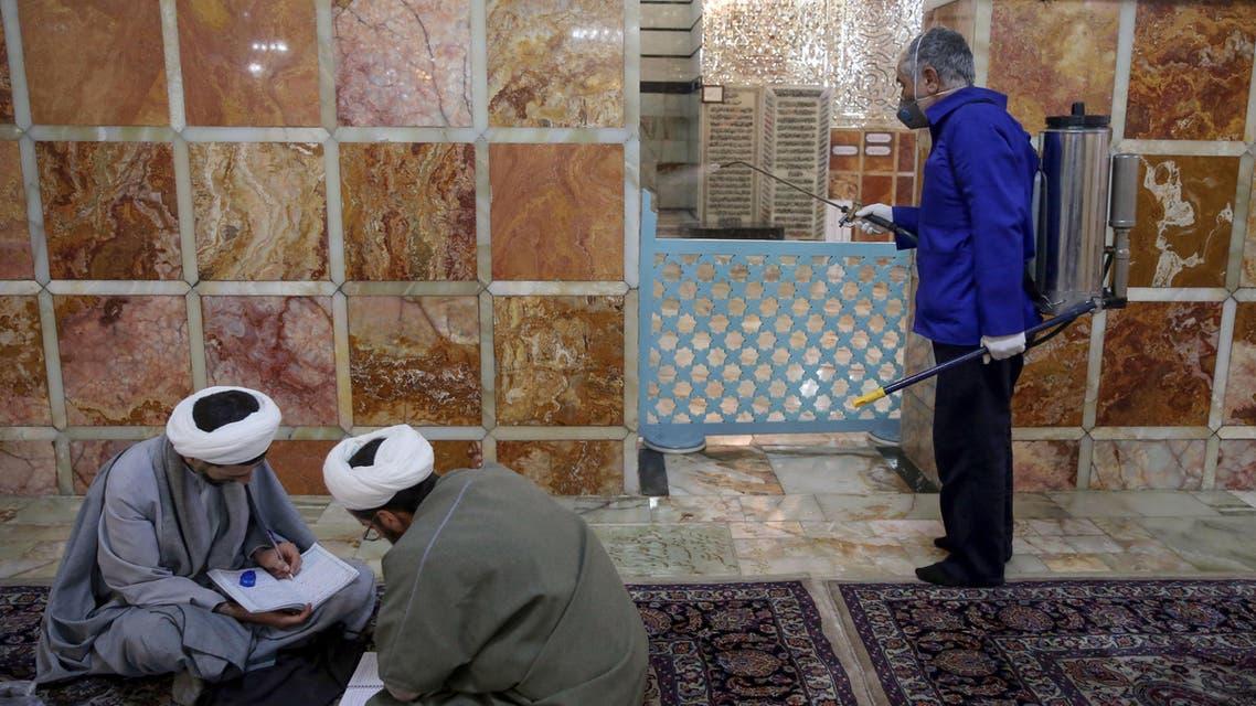An Iranian sanitary worker disinfects Qom's Masumeh shrine on February 25, 2020. (AP)
