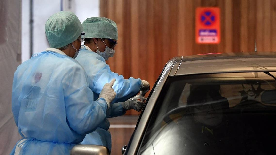 """Medical staff take samples to a driver at a """"drive-through"""" testing facility for the novel coronavirus at the """"Hopital de la Citadelle"""" hospital in Liege, on it's opening day on March 10, 2020. (AFP)"""