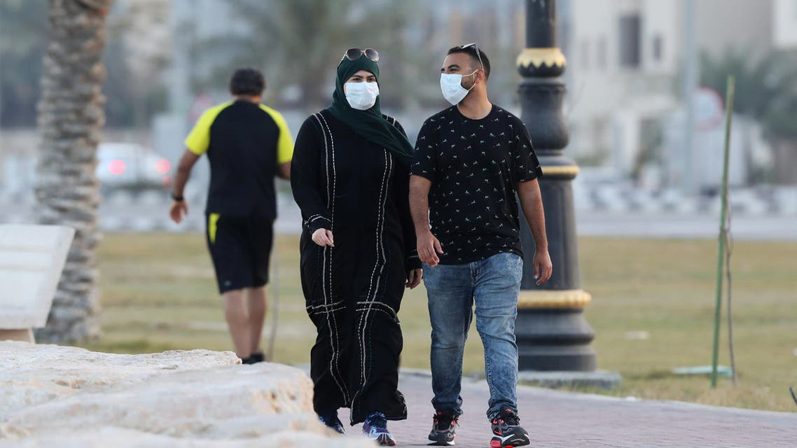 A couple wear a protective face mask, as they walk, after Saudi Arabia imposed a temporary lockdown on the province of Qatif, following the spread of coronavirus, in Qatif, Saudi Arabia, March 10, 2020. (Reuters)