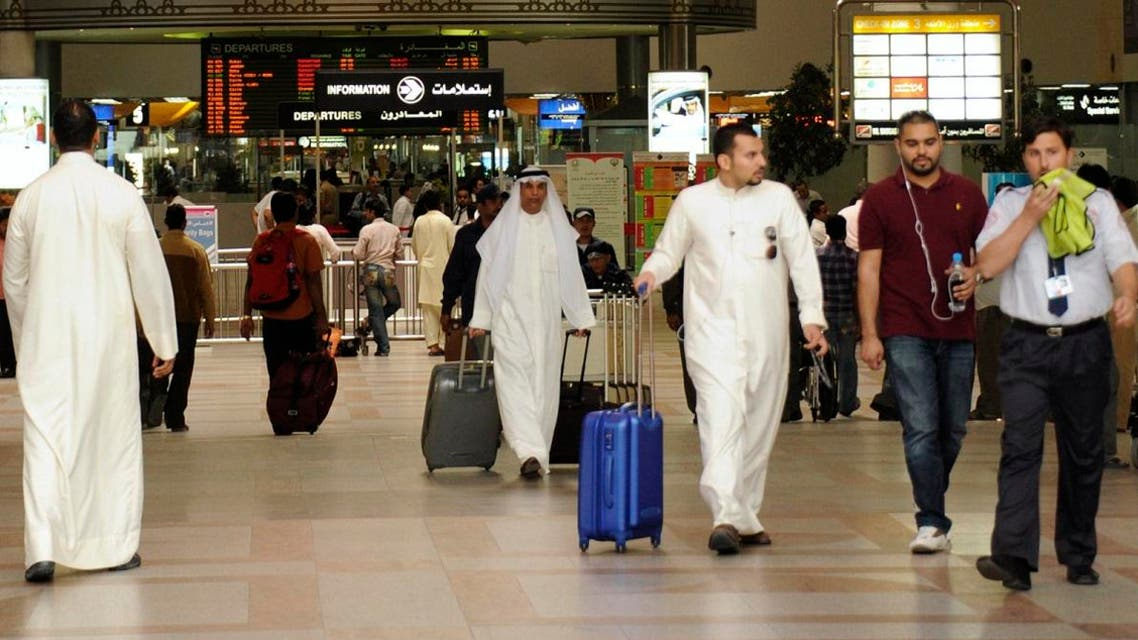 Passengers walk under the flight schedule board showing several cancelled flights, in Kuwait International Airport. (File photo: Reuters)