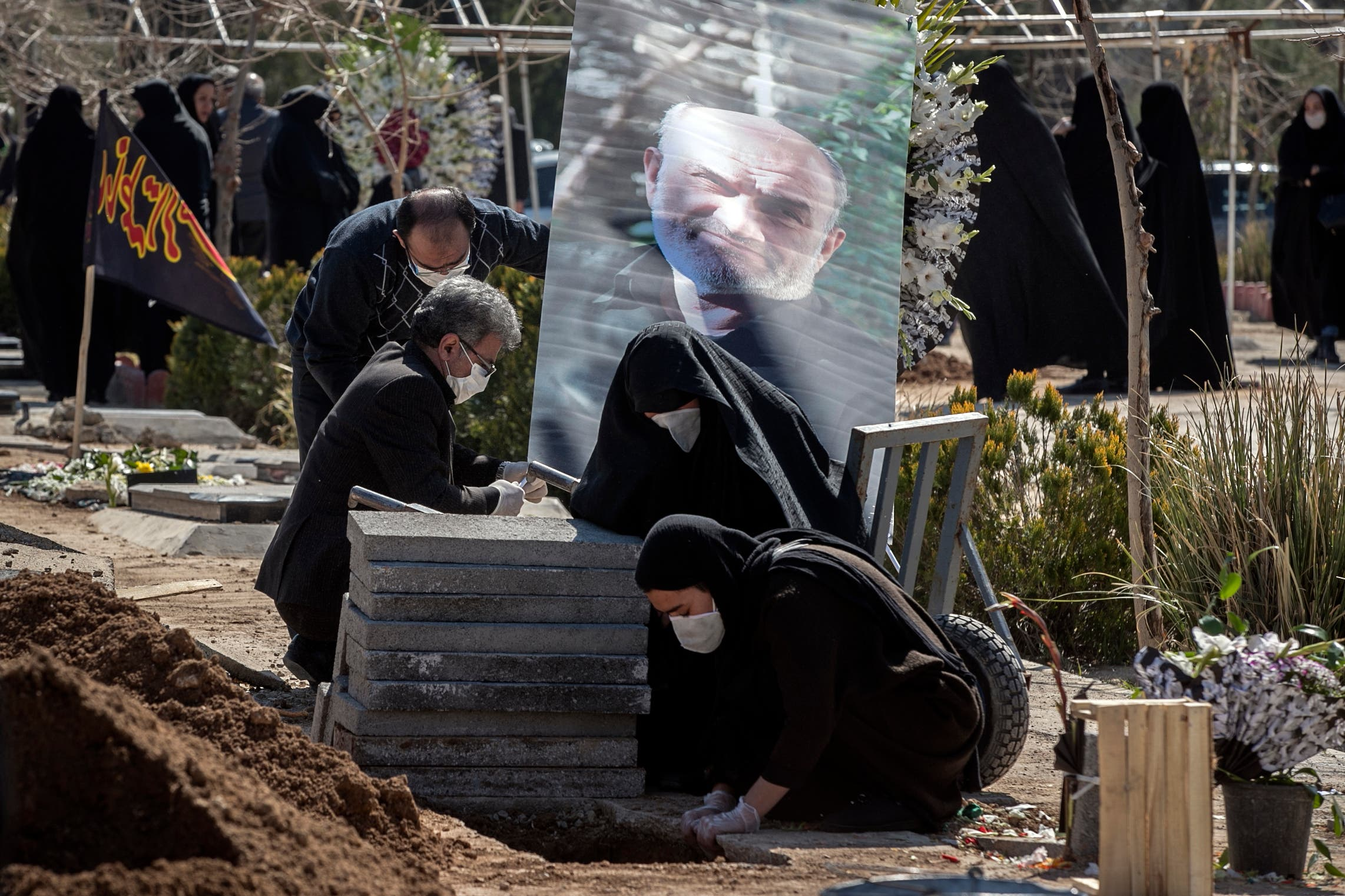Relatives mourn over the grave of former politburo official in the Revolutionary Guard Farzad Tazari who died after being infected with the coronavirus just outside Tehran on March 10, 2020. (AP)