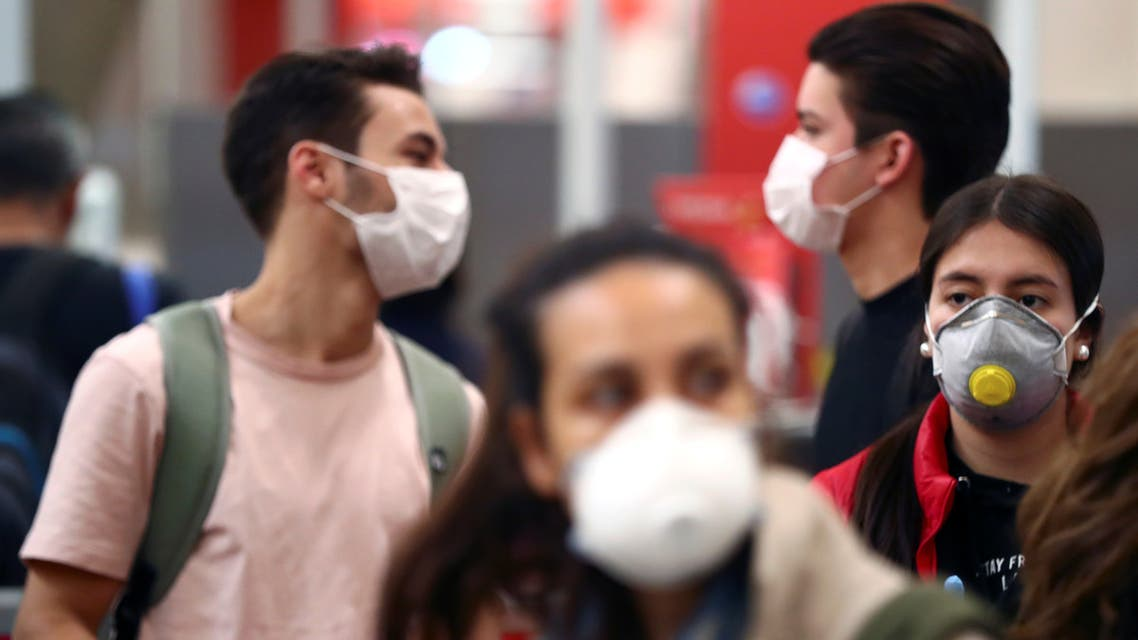Passengers, wearing protective face masks, wait for checking-in before boarding their flights to the U.S. at Madrid's Adolfo Suarez Barajas airport, Spain March 12, 2020. REUTERS/Sergio Perez