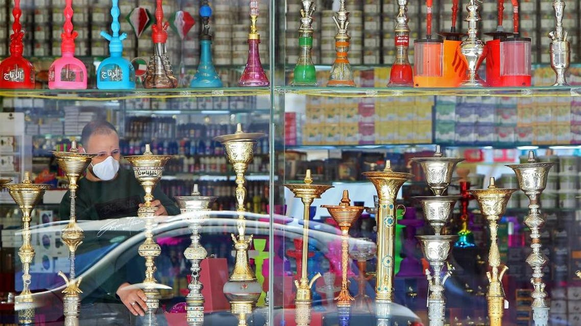 A cigarette and hookah seller wearing a protective mask looks through the front of his store in Kuwait City on March 5, 2020. (AFP)