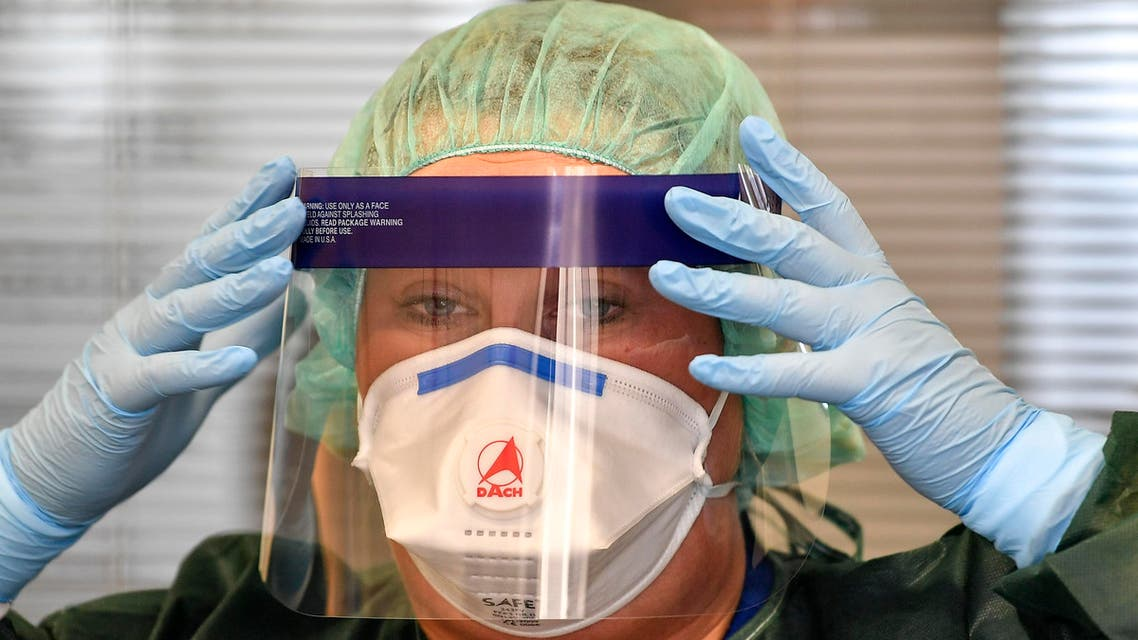 A nurse prepares her mask before she demonstrates a coronavirus test at the infection station of the university hospital in Essen, Germany, on March 12, 2020. (AP)