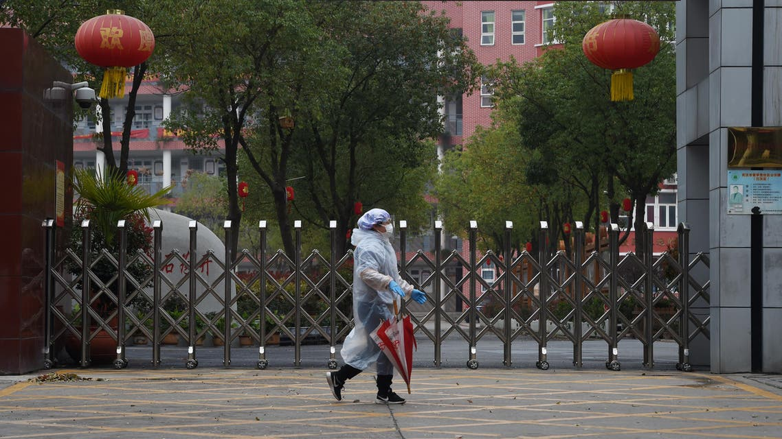 A resident in protective gear walks past the entrance of a closed secondary school in Wuhan, the epicentre of the novel coronavirus outbreak, Hubei province, China March 9, 2020. REUTERS