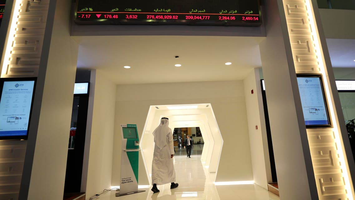 An Emirati trader passes under the stocks display screen at the Dubai Financial Market in Dubai, United Arab Emirates, Sunday, March 8, 2020. (AP)