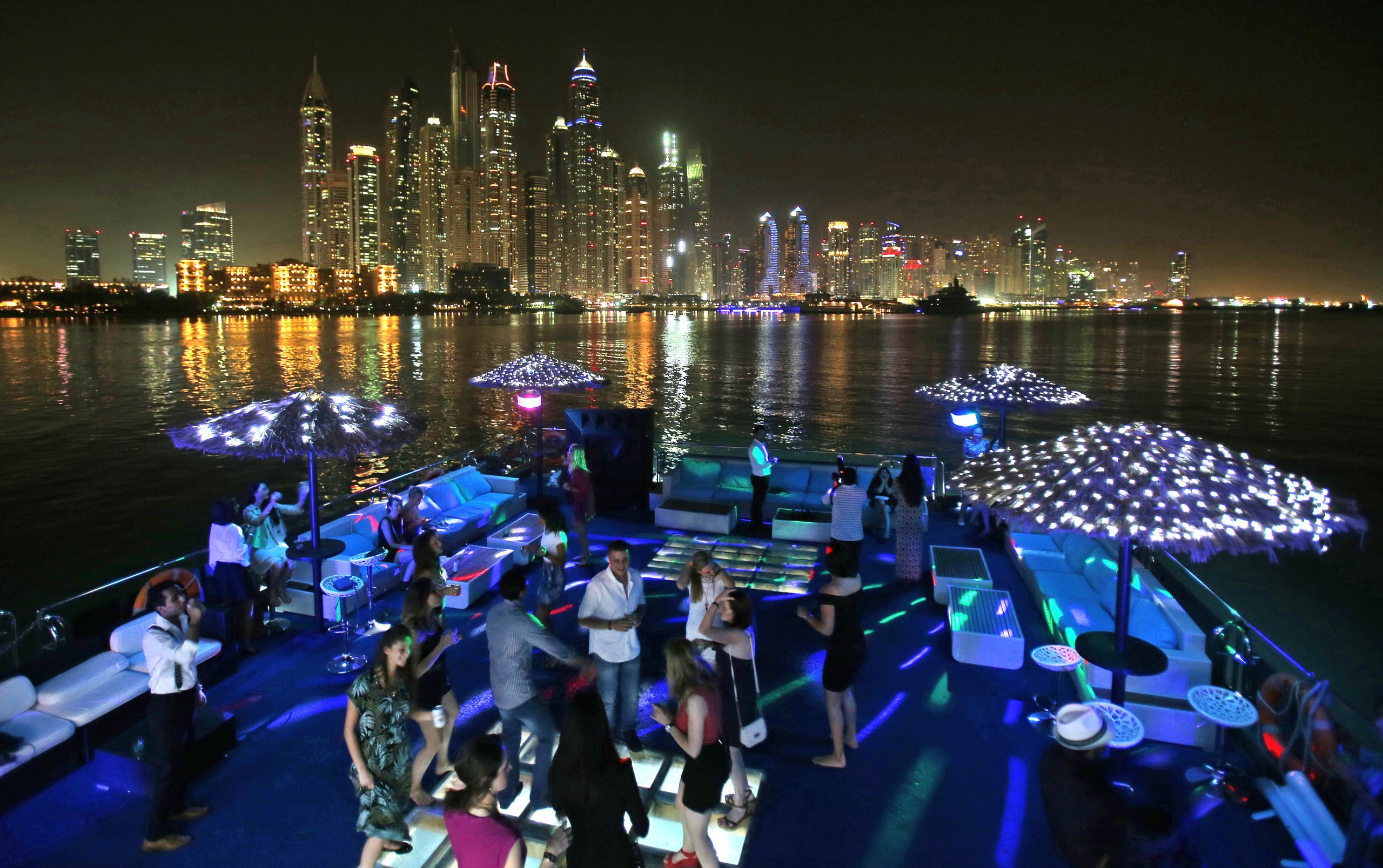 Guests dance during a private party opposite the skyline of the Marina Waterfront in Dubai, United Arab Emirates. (File photo: AP)