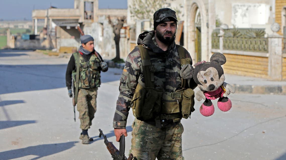 A Turkey-backed Syrian fighter holds a stuffed toy in the town of Saraqib in the eastern part of the Idlib province in northwestern Syria, on February 27, 2020. Syrian rebels reentered the key northwestern crossroads town of Saraqib lost to government forces earlier this month but fierce fighting raged on in its outskirts today, an AFP correspondent reported.