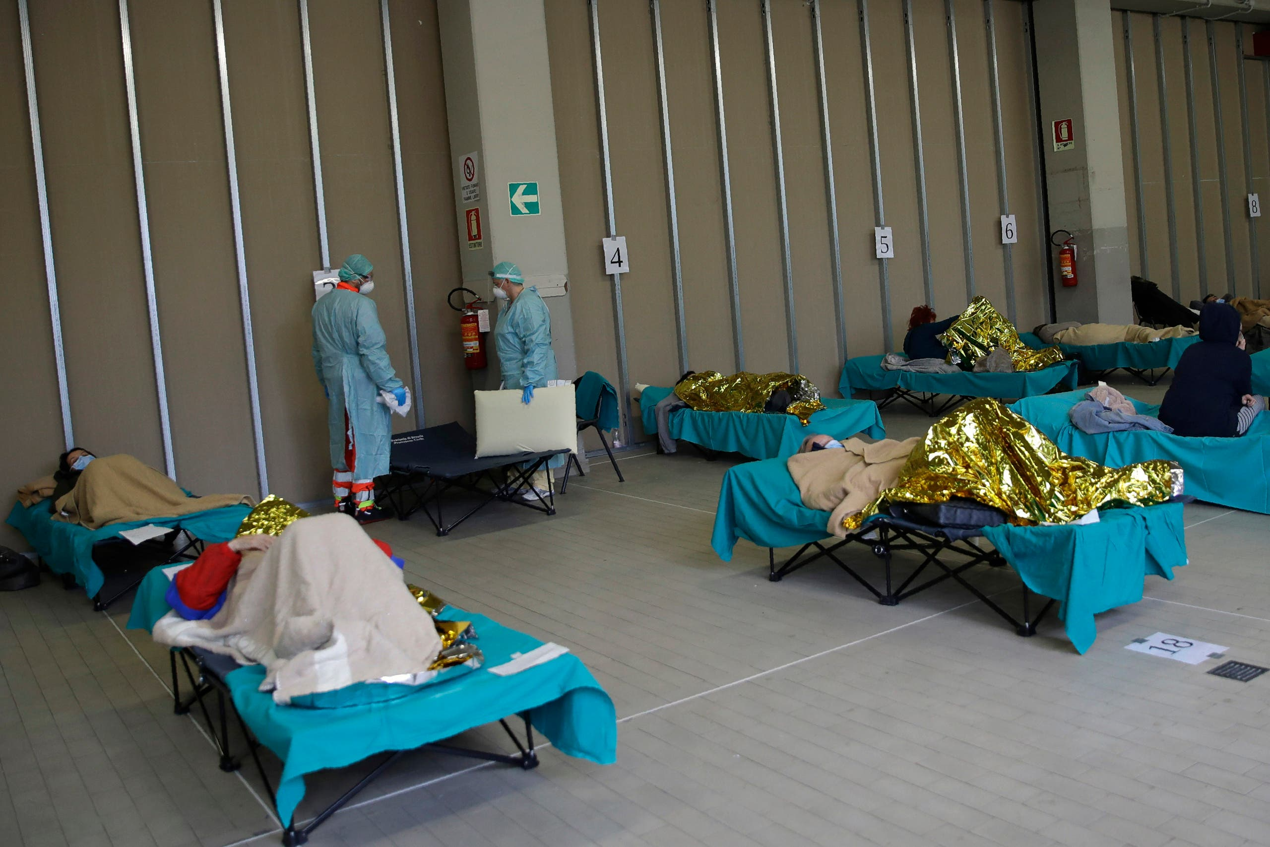 Patients lie on beds at one of the emergency structures that were set up to ease procedures at the Brescia hospital, northern Italy on March 12, 2020. (AP)