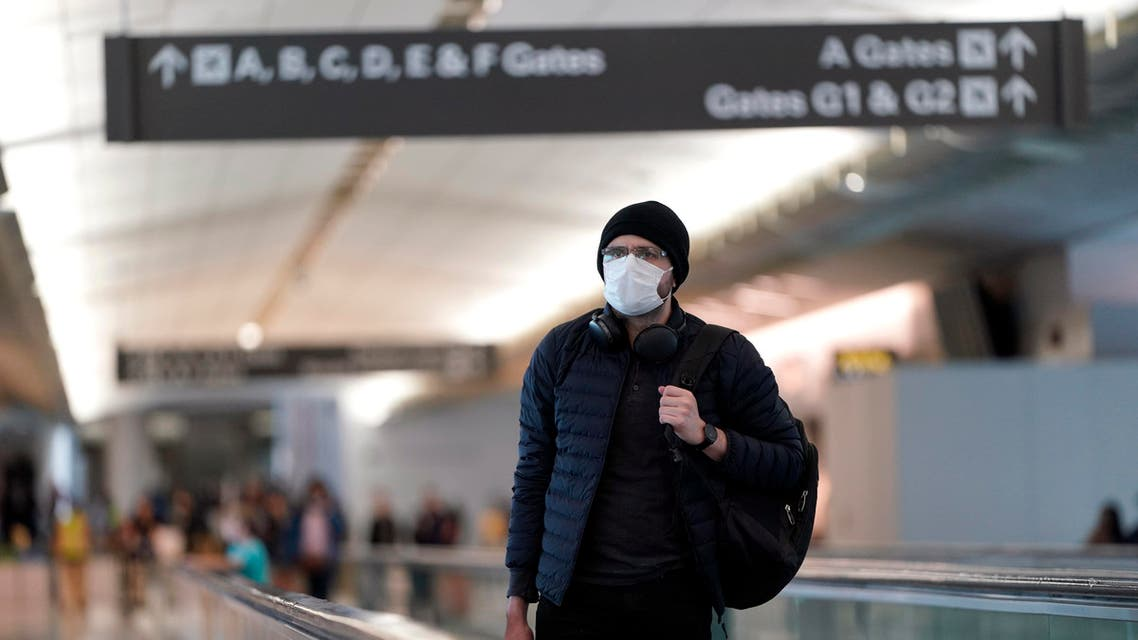An airline passenger wearing a mask makes his way through the International Terminal at San Francisco International Airport Saturday, March 7, 2020, in San Francisco. (AP)