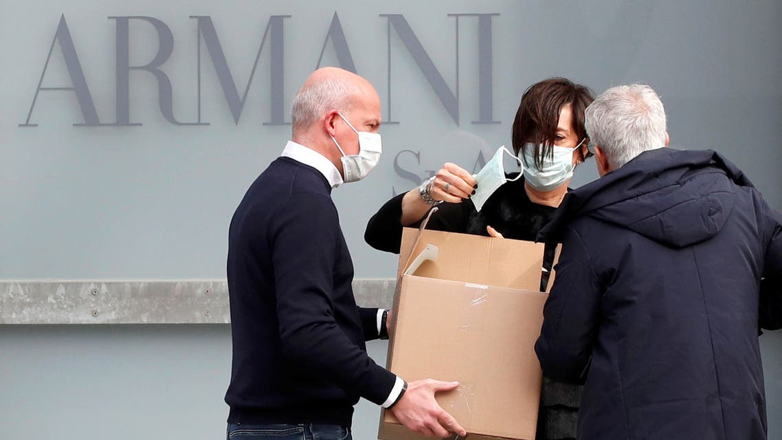 A worker holds a face mask outside the theatre where the Italian designer Giorgio Armani said his Milan Fashion Week show would take place to safeguard the health of press and buyers after a coronavirus outbreak in northern Italy, in Milan, Italy, February 23, 2020. REUTERS/Alessandro Garofalo