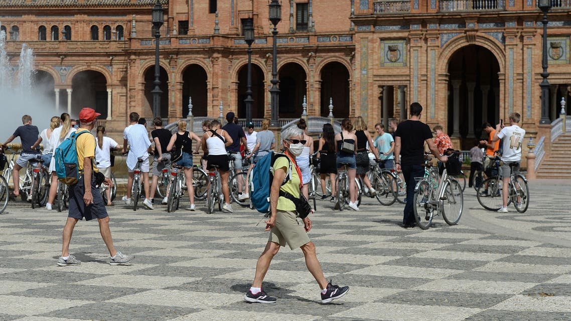 A tourist wearing a protective mask walks at Plaza de Espana in Seville on March 11, 2020 after Spain banned all air traffic from Italy, closed schools and blocked fans from football matches due to the coronavirus outbreak. (AFP)