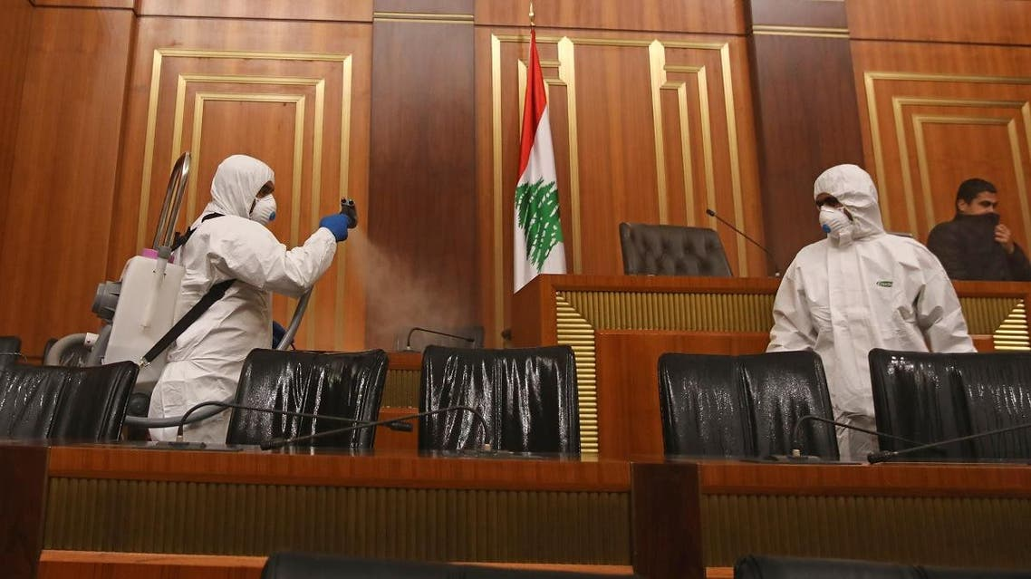Sanitary workers disinfect the desks and chairs of the Lebanese Parliament in central Beirut on March 10, 2020 amid the spread of coronavirus in the country.  (AFP)