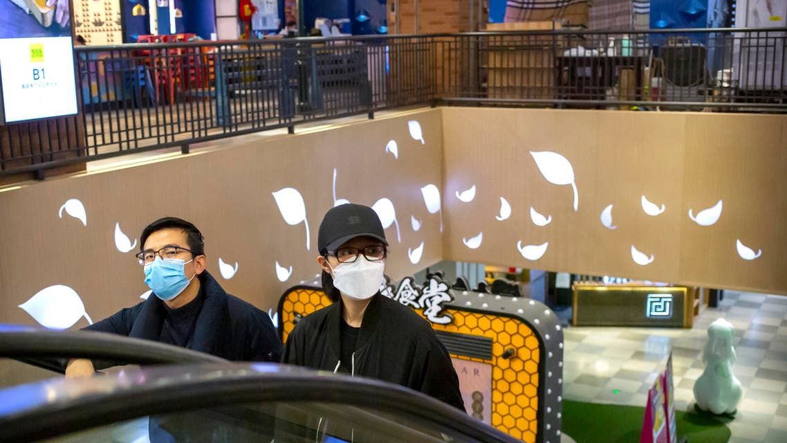 A couple wear face masks as they ride an escalator at a shopping mall in Beijing, Saturday, March 7, 2020.