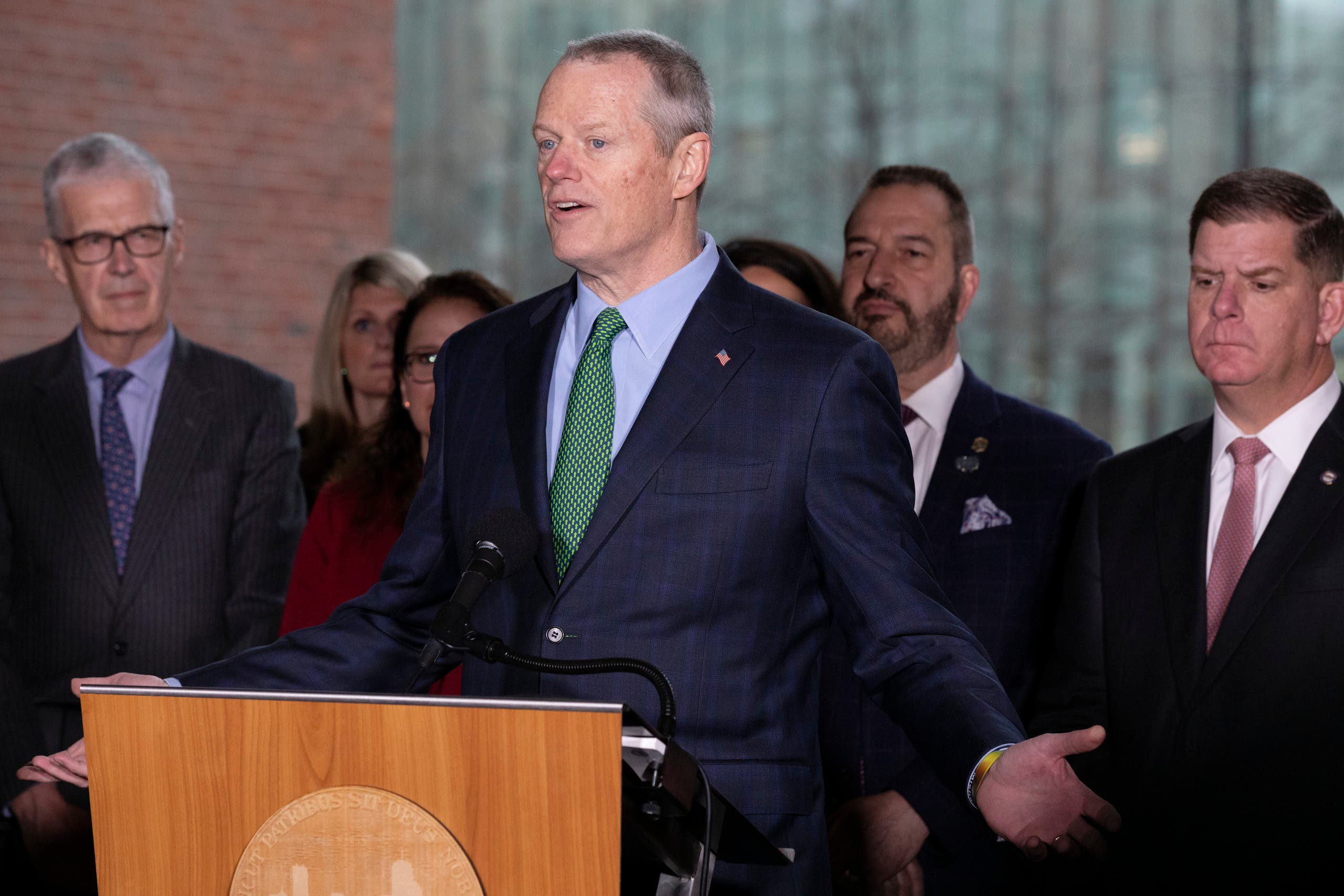 Massachusetts Governor Charlie Baker, center, speaks during a news conference outside Boston City Hall in front of Mayor Marty Walsh, right, and CEO of the Boston Athletic Association Thomas Grilk, left, on Friday, March, 13, 2020, in Boston. (AP)