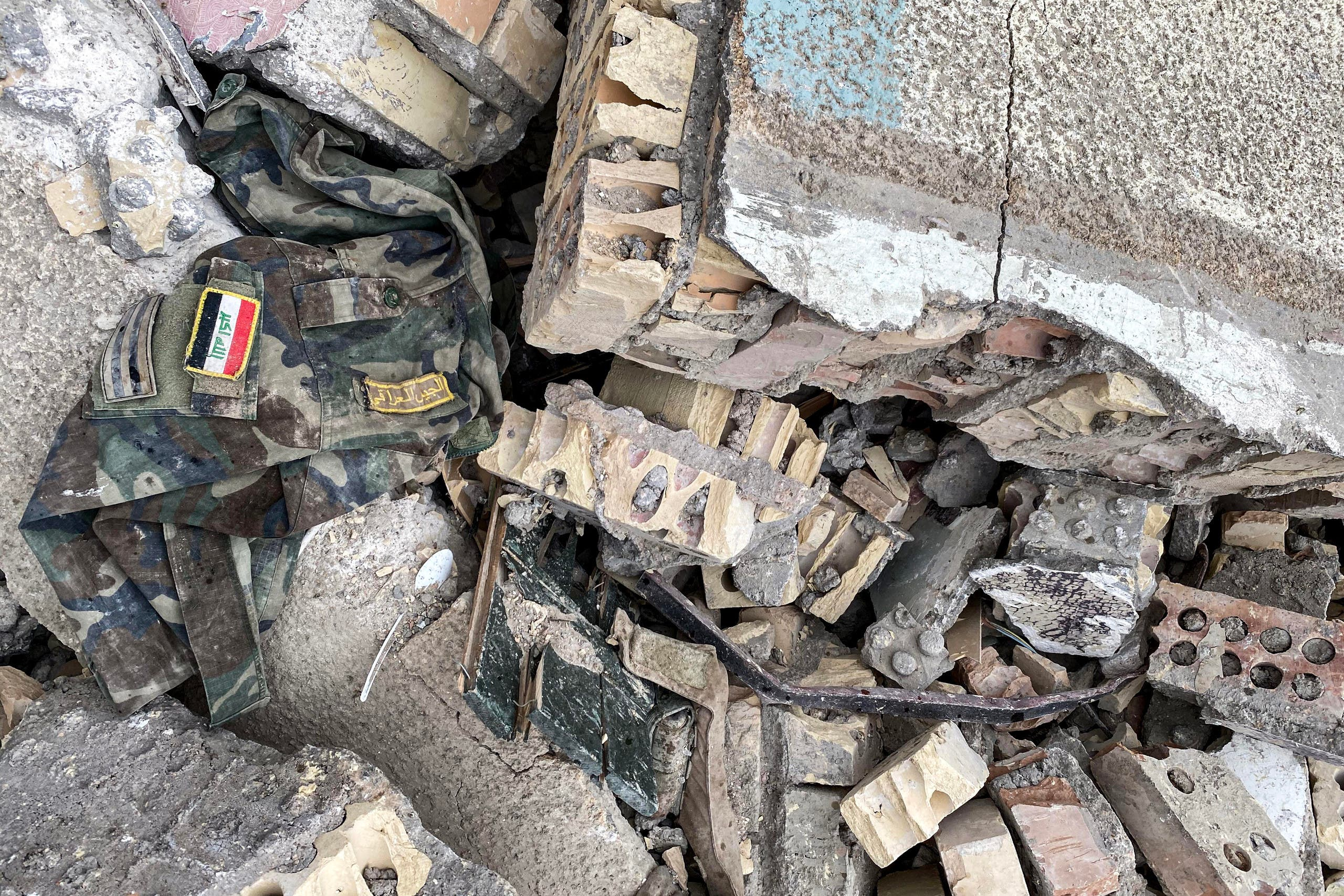This picture taken on Friday shows a military uniform bearing in the insignia 'Iraqi Army' amidst rubble in the aftermath of US military air strikes at a militarized zone in the Jurf al-Sakhr area in Iraq's Babylon province controlled by Kataeb Hezbollah (AFP