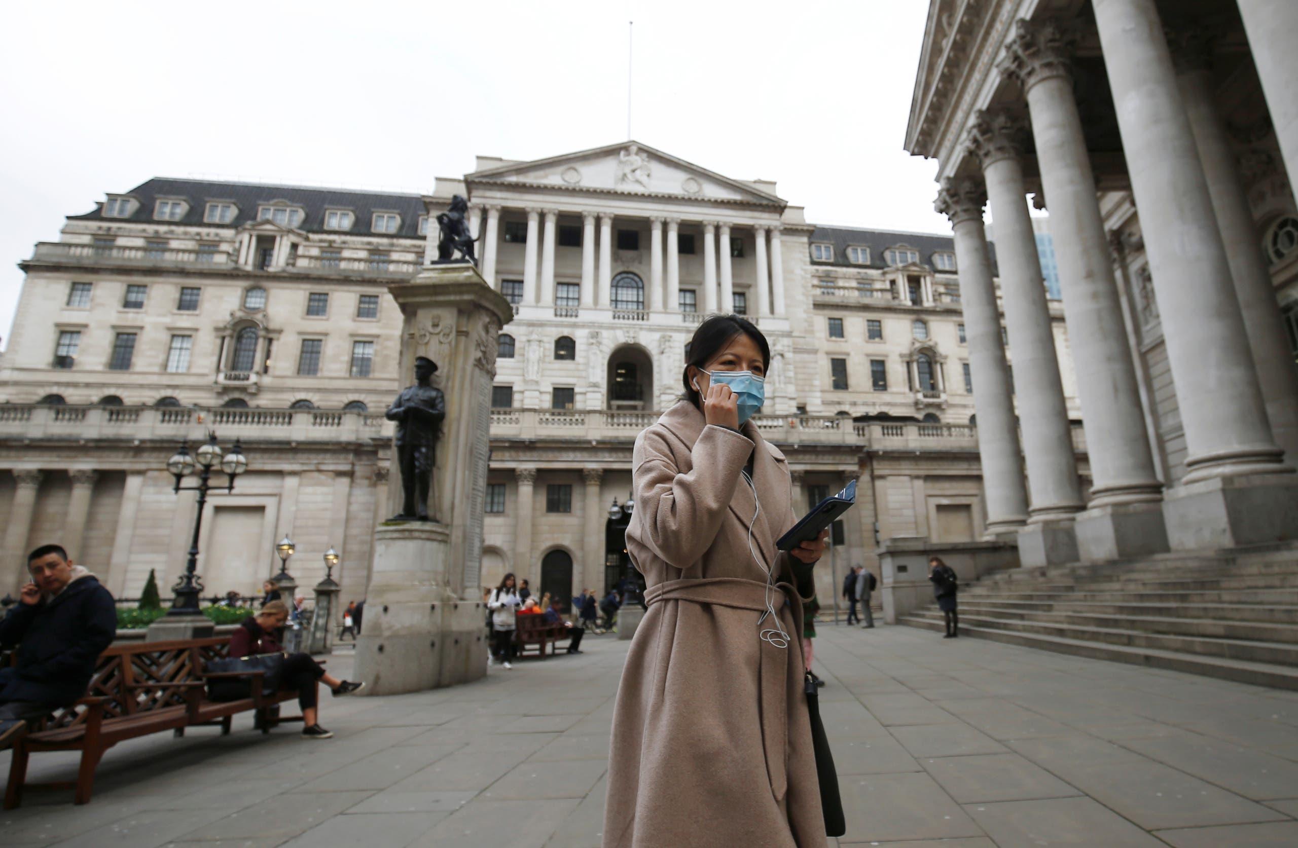 امرأة تضع قناعاً واقياً في لندن الأربعاء