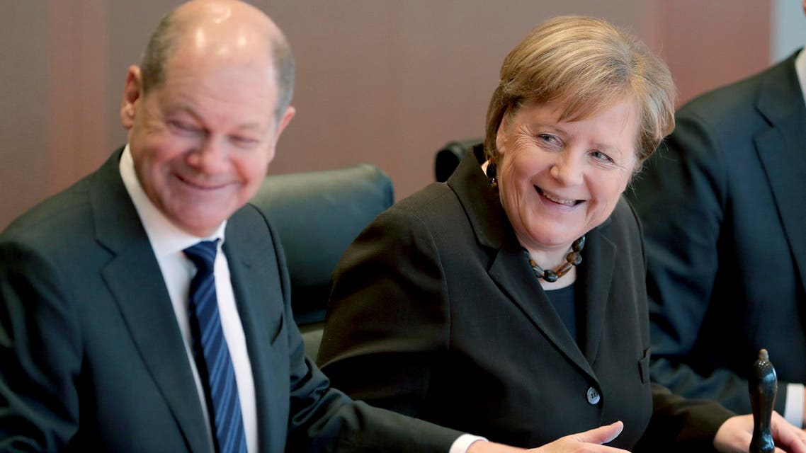 German Chancellor Angela Merkel, right, smiles as she and German Finance Minister Olaf Scholz, left, arrive for the weekly cabinet meeting at the Chancellery in Berlin, Germany, on Wednesday, February 19, 2020. (AP)