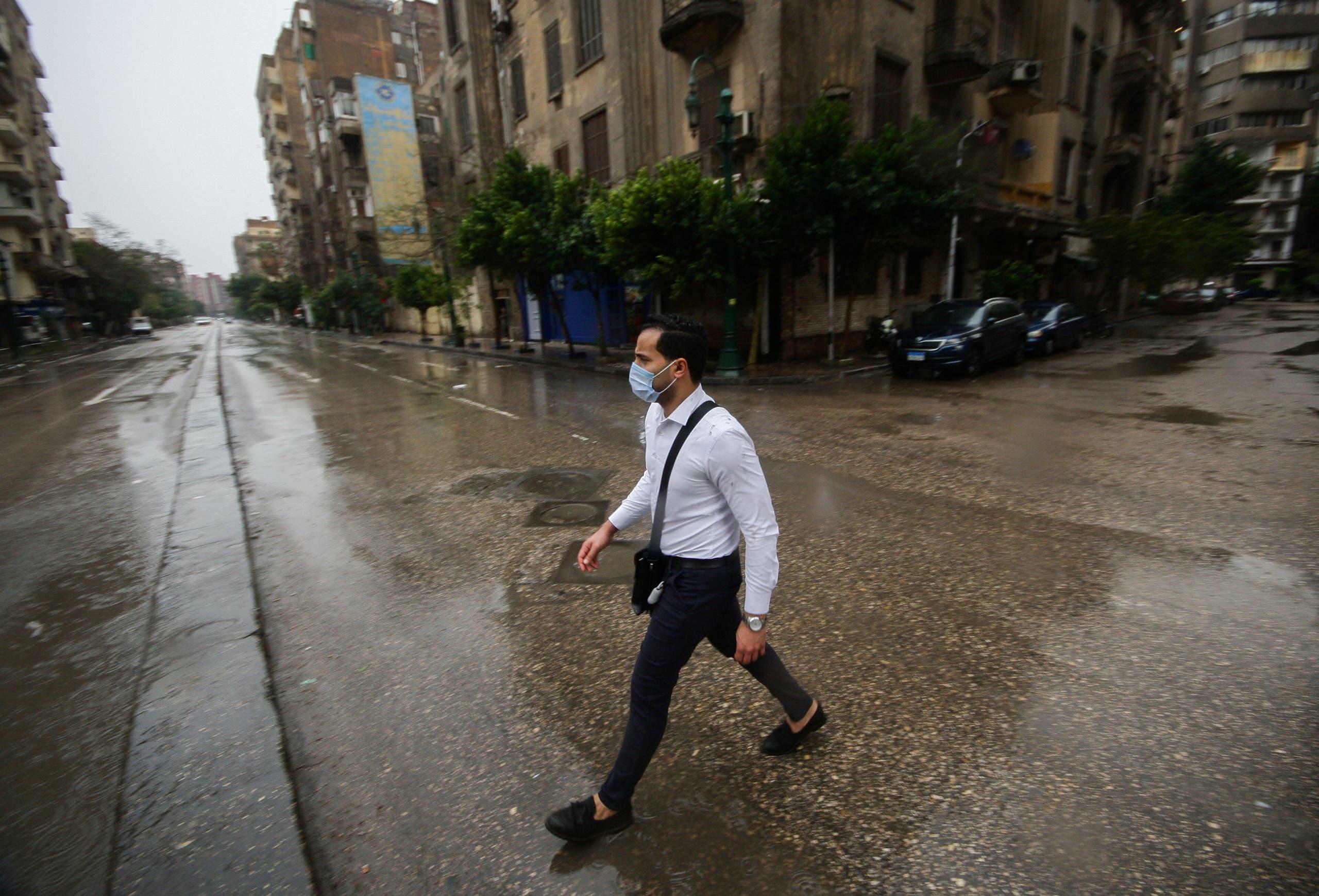 رجل يضع قناعا واقيا في وسط القاهرة