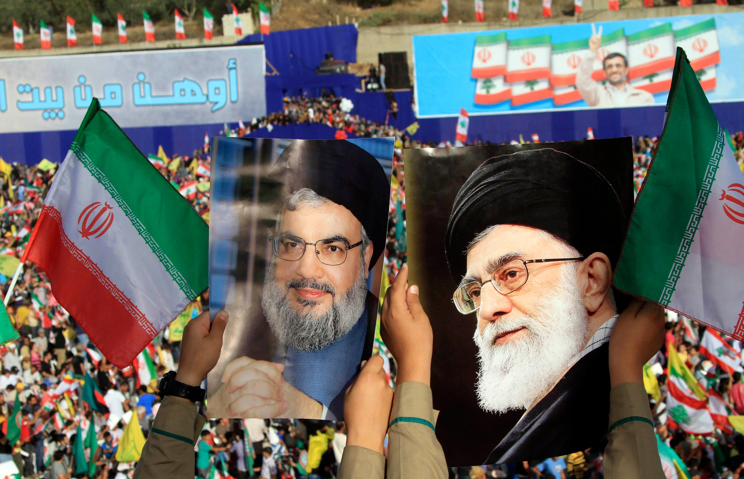 Two boys carry pictures of Hezbollah leader Hassan Nasrallah, left, and Iranian Supreme Leader Ali Khamenei in the southern town of Bint Jbeil, Lebanon. (File photo: AP)