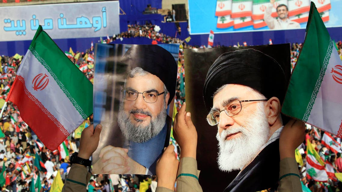 Two boys carry pictures of Hezbollah leader Hassan Nasrallah, left, and Iranian Supreme Leader Ayatollah Ali Khamenei, right, as thousands of Hezbollah supporters gather in a soccer field to listen to Iranian President Mahmoud Ahmadinejad 's speech during a rally in the southern town of Bint Jbeil, Lebanon on Oct. 14, 2010. (AP)