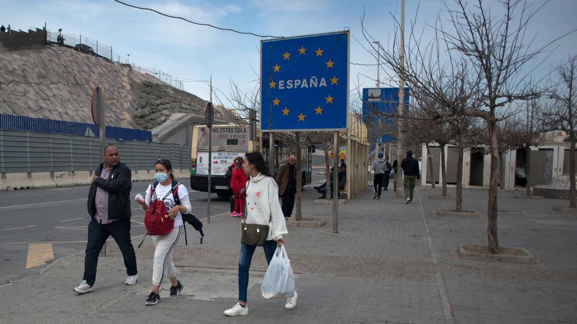 People walk near the Spanish border with Morocco in Ceuta. Morocco suspended air and sea links with France and Spain, and closed its border with two Spanish North African enclaves, officials said. (AFP)