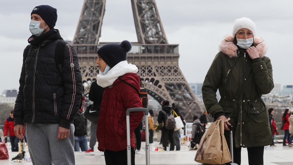 People walk near the Eiffel Tower wearing protective face masks amid the outbreak of COVID-19, the new coronavirus, on the Trocadero esplanade in Paris, on March 10, 2020.
