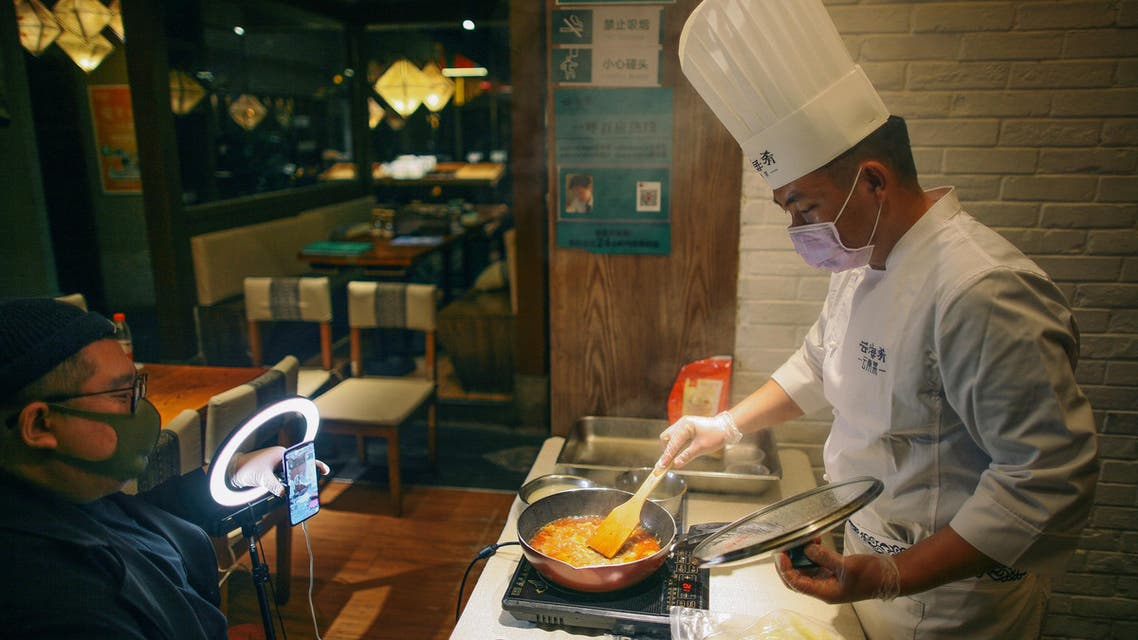 Chef wearing a face mask conducts a cooking lesson through a live-streaming session inside a restaurant at a shopping complex, as the country is hit by an outbreak of the novel coronavirus (COVID-19), in Tianjin. (Reuters)
