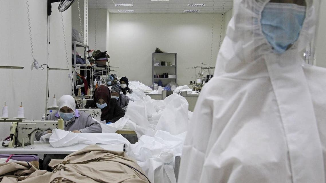 Workers produce protective clothing at a textile factory in the southern Lebanese city of Sidon on March 14, 2020. (AFP)