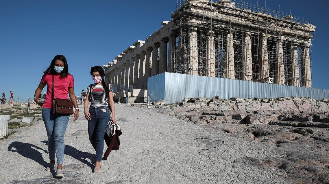 Visitors wear protective face masks as they walk past the ancient Parthenon temple at the archaeological site of the Acropolis in Athens. (Reuters)