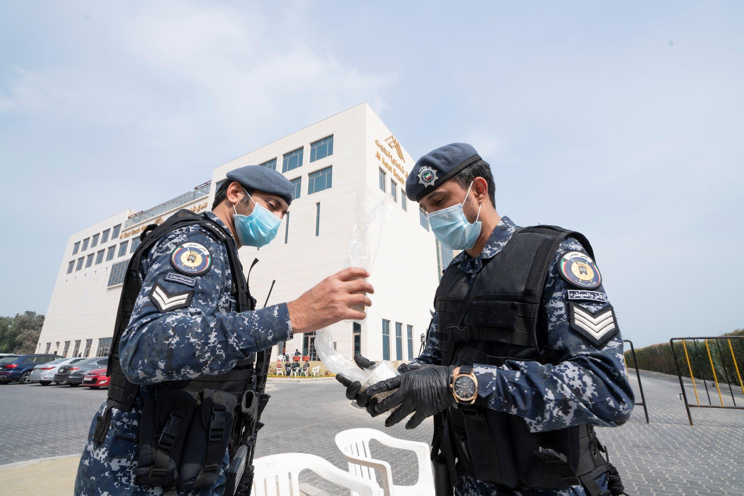 عناصر شرطة أمام فندق يقيم فيه أشخاص عائدون للكويت من إيران في إطار الحجر الصحي للتأكد من خلوهم من فيروس كورونا
