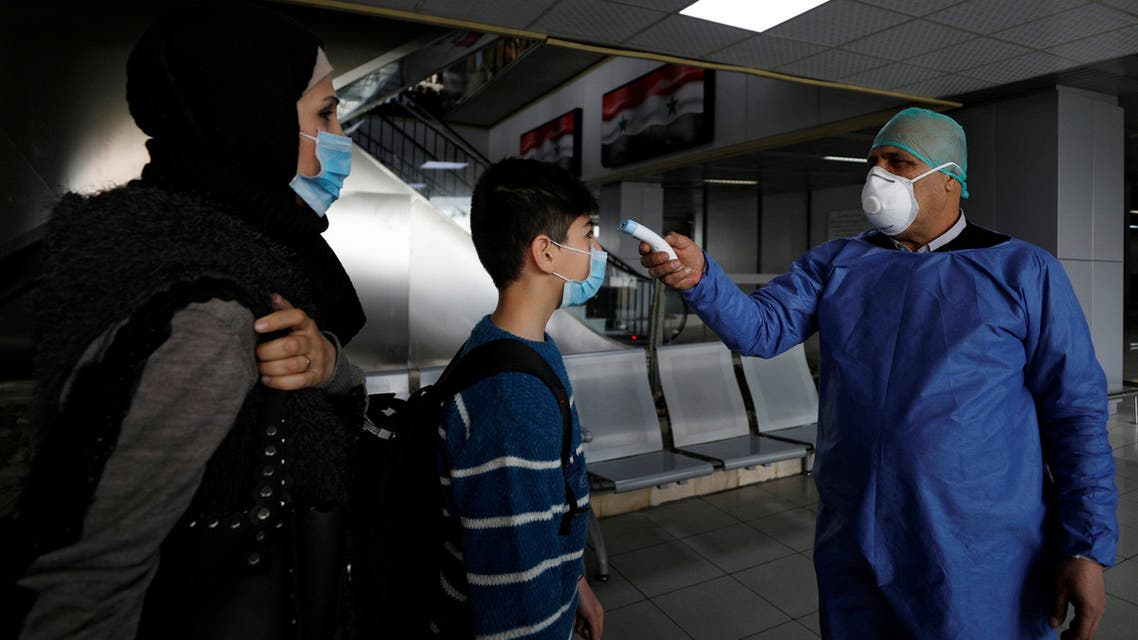 Health officials wait to test passengers as part of security measures to avoid coronavirus in the country at Damascus international airport, Damascus Syria March 9 2020