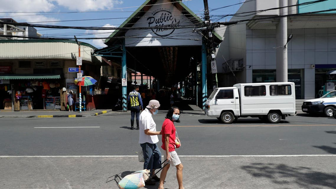 People wearing protective masks walk past a public market in Marikina, Philippines, Friday, March 13, 2020. (AP)