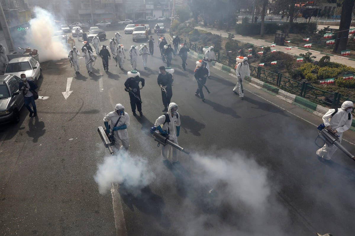 Firefighters disinfect a square against the new coronavirus, in western Tehran, Iran, Friday, March 13, 2020. (AP)