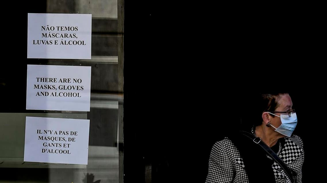 A woman wearing a face mask exits a pharmacy bearing warnings at the entrance about the end of stocks of masks, gloves and alcohol in downtown Lisbon on March 14, 2020. (AFP)