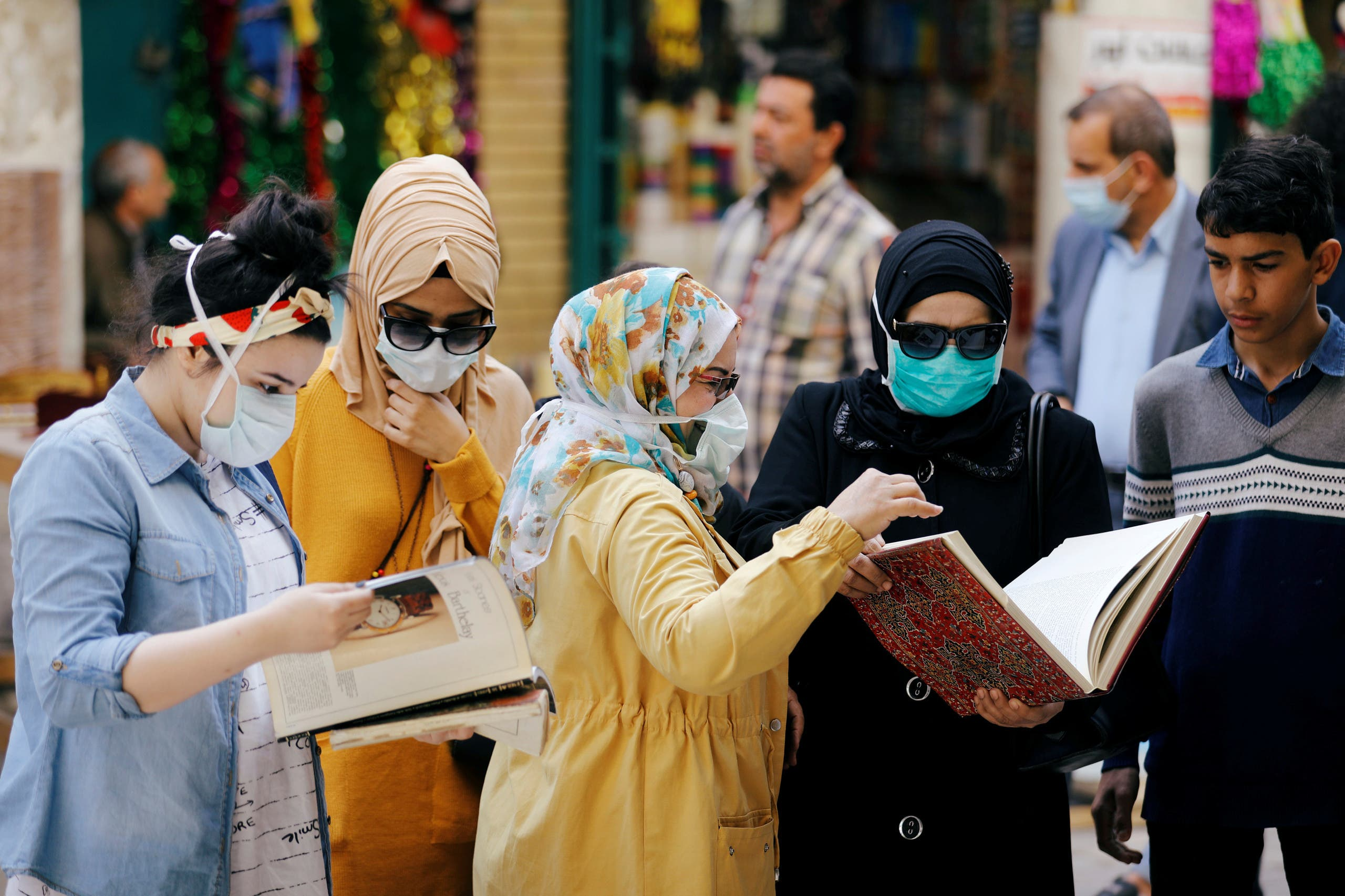 عراقيات يرتدين كمامات خلال تصفحهن كتباً في أحد أسواق بغداد