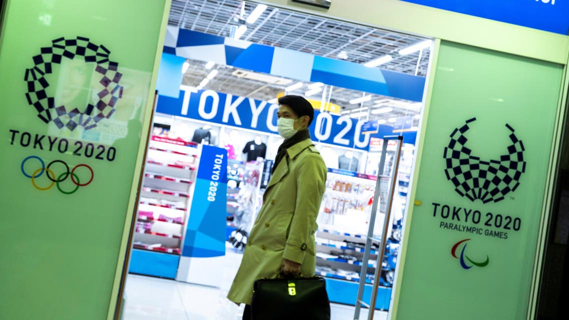 A man wearing a protective face mask, following an outbreak of the coronavirus disease (COVID-19), walks past a Tokyo Olympics 2020 souvenir shop in Tokyo, Japan, March 13, 2020. Picture taken March 13, 2020. REUTERS/Athit Perawongmetha