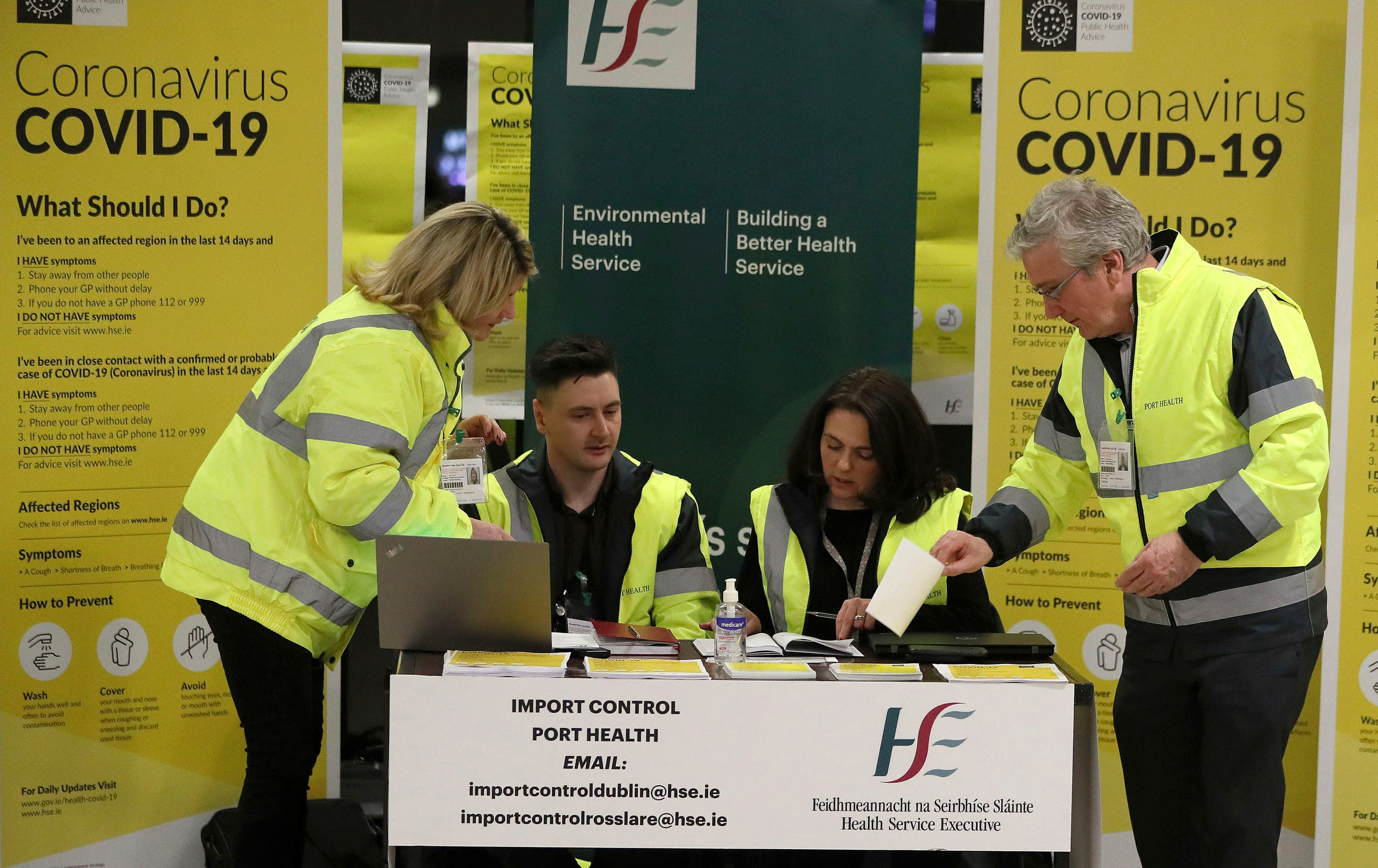Staff conduct a public awareness campaign for COVID-19 in the baggage hall of Terminal 2 at Dublin Airport in Dublin on Feb. 28, 2020. (AP)
