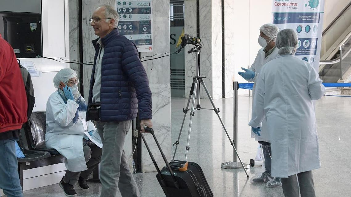 Health personnel monitor a thermal scanner as passengers arrive at Tunis-Carthage Airport in the Tunisian capital Tunis on March 10, 2020. (AFP)