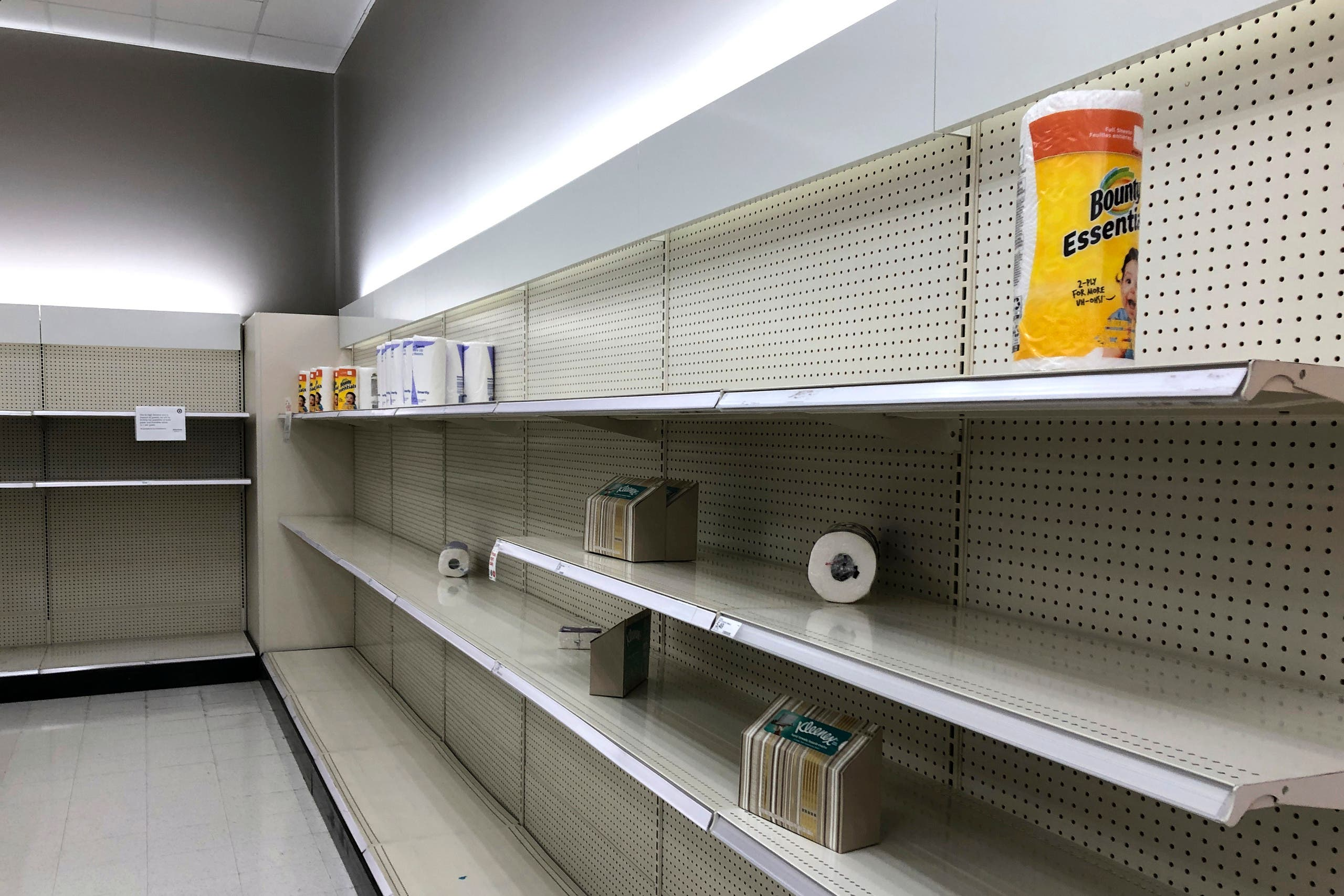 Shoppers walk through nearly empty shelves that usually hold toilet paper and paper towels, on March 14, 2020, in a Target store in Olympia, Washington. (AP)