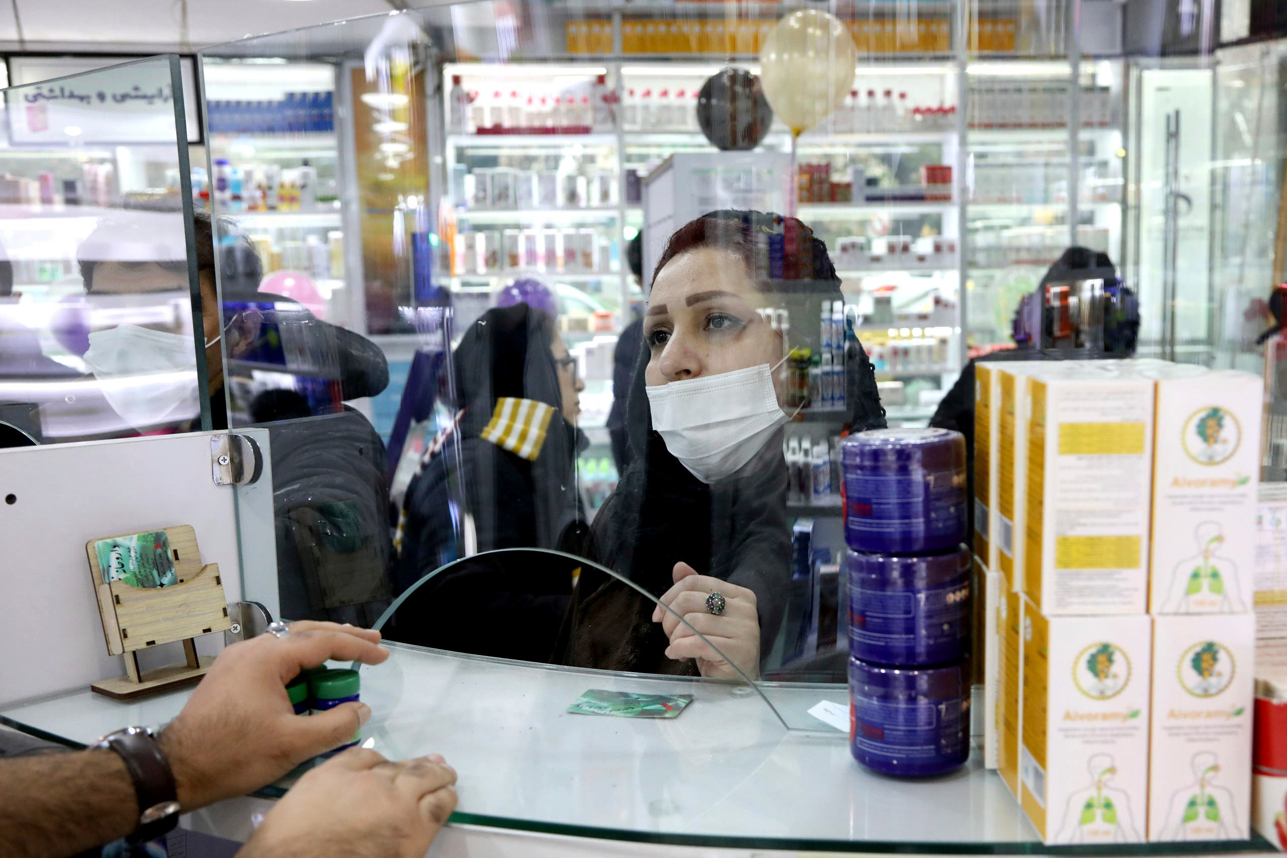A customer talks with a pharmacist at a drugstore in Tehran on Feb. 25, 2020. (AP)