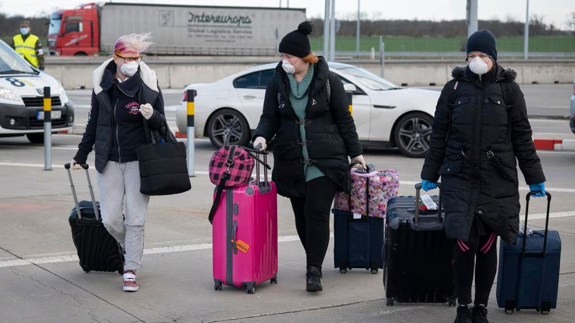 Women wearing a protective facemask due to the coronavirus COVID-19 cross the Bratislava-Jarovce border crossing between Austria and Slovakia. (AFP)