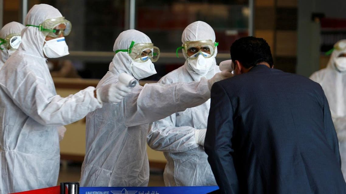 Iraqi medical staff check passengers' temperature, amid coronavirus outbreak, upon their arrival from Iran, at Najaf airport, Iraq March 5, 2020. (Reuters)