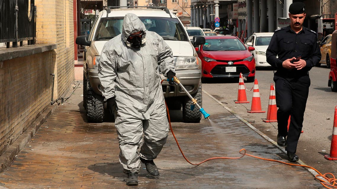 A civil defense worker sprays disinfectant as a precaution against the coronavirus in Baghdad on March 11, 2020. (AP)